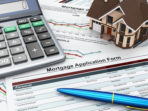 Mortgage application form with a calculator and mini house model