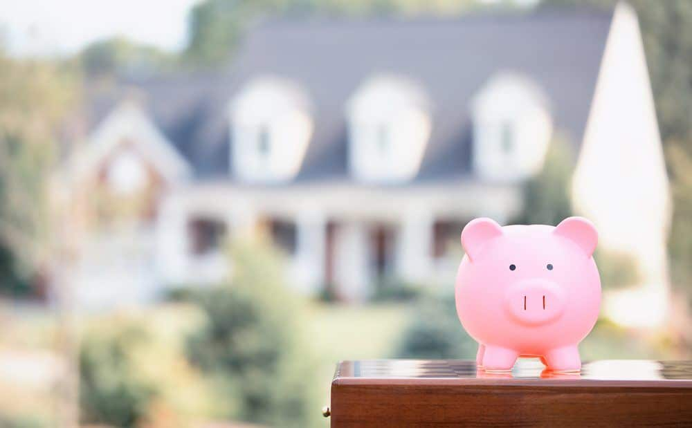 House blurred in background behind pink piggy bank, mortgage concept
