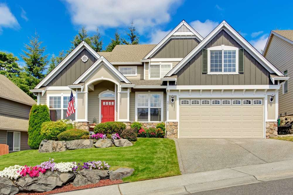 Grey house exterior with entrance porch and red door. Beautiful front yard landscape with vivid flower and stones