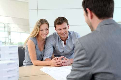 smiling young couple looking at home documents and talking to lender