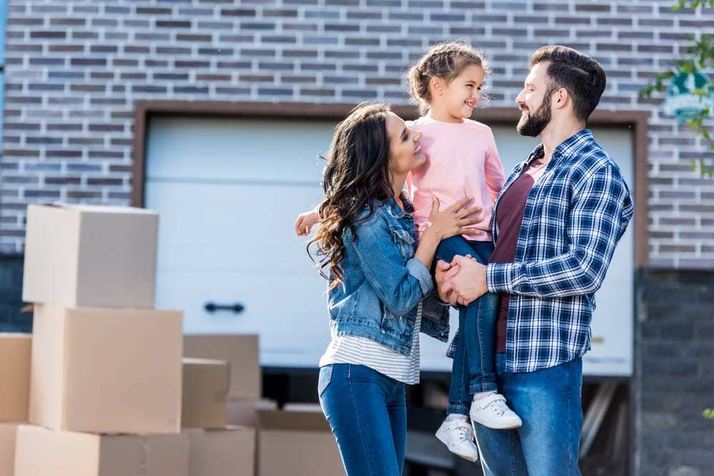 young couple and daughter smiling in front of moving boxes at new house
