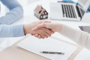 Close-up of two women shaking hands over desk with paper, pen, laptop, and house model