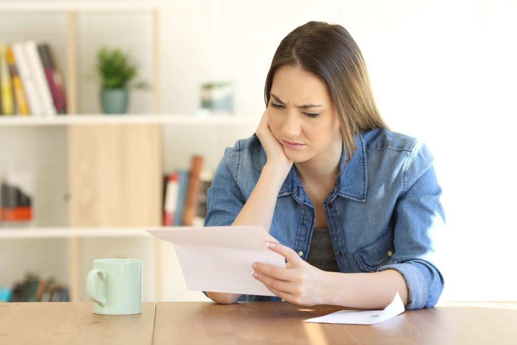 Worried young woman looking at paper at home