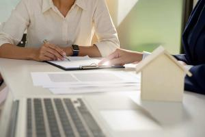 Woman filling out papers on desk, realtor assisting, house model in foreground