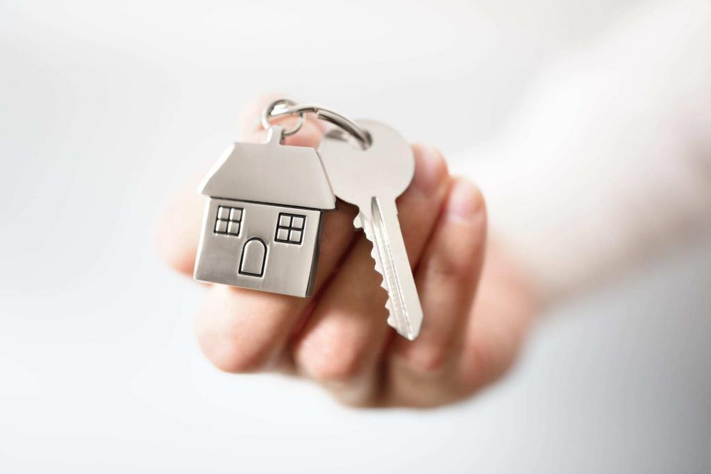 Close-up of hand holding key and house keychain