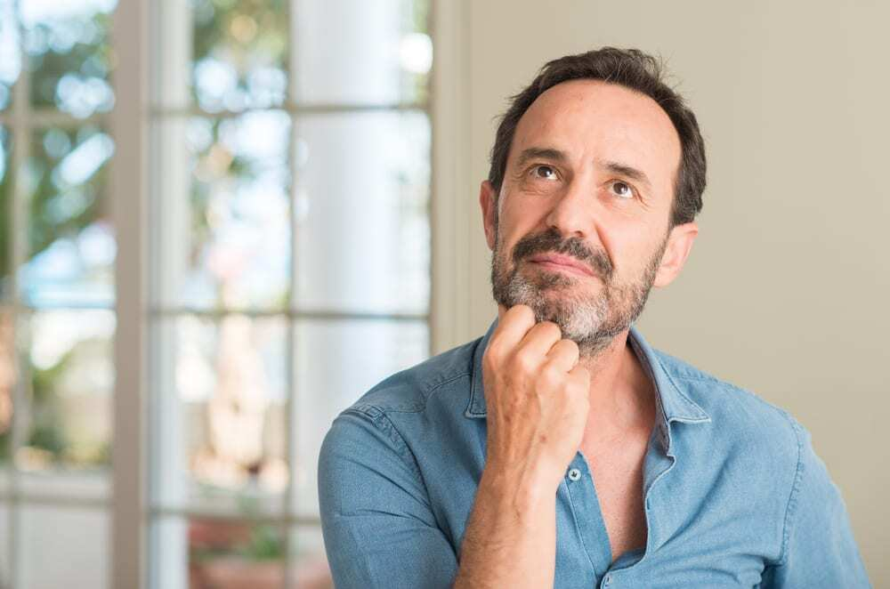 Middle-aged man inside home looking pensive