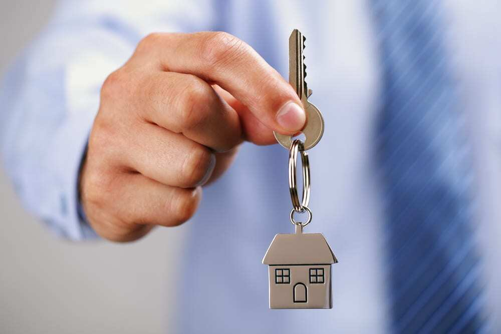 Close-up of hand holding out key attached to house keychain