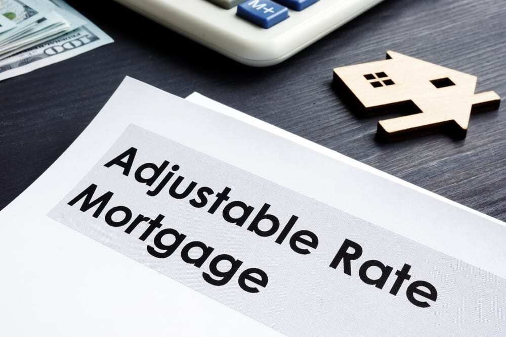 """Paper reading """"Adjustable Rate Mortgage"""" beside calculator, cash, and tiny wooden house"""
