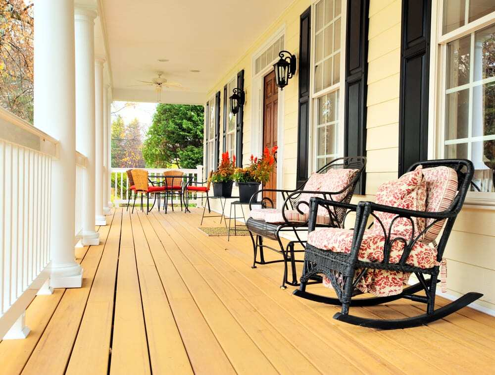 Rocking chairs, table, and plants on traditional front porch