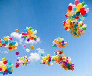 Colorful balloons in bunches soaring through the sky