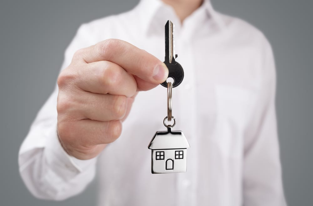 Close-up of man holding out house key