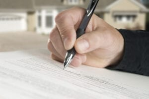 Close-up of hand writing with pen on housing document, blurry home in background