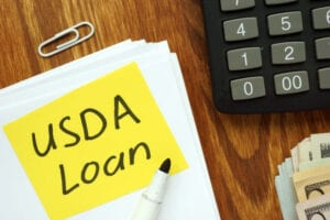USDA loan written on post-it beside calculator, cash, pen, paper clip