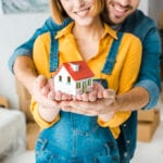 Close-up of young couple holding house model together