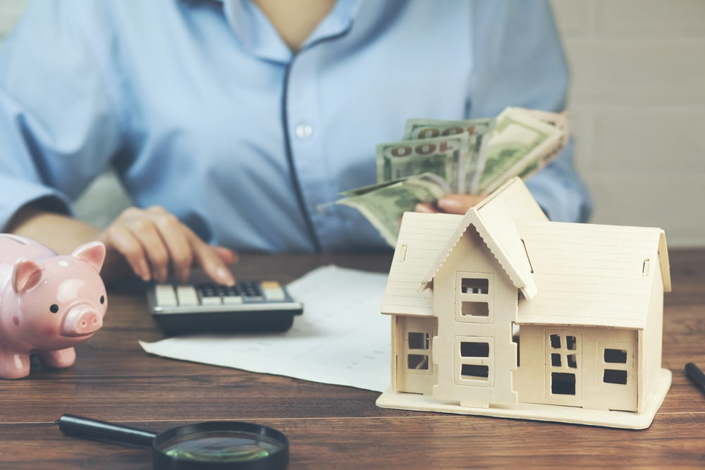 Close-up of person holding cash, typing on calculator, small house model on table