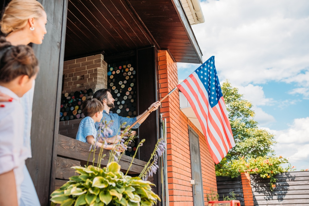 Family on home porch, father putting american flag in place