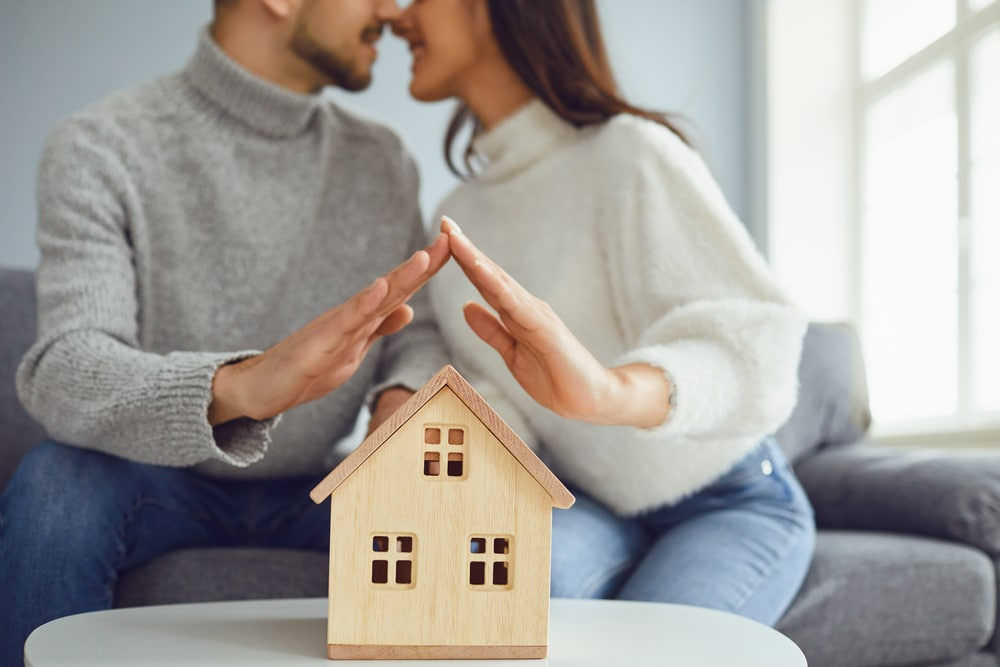 Young couple about to kiss, hands hovering above wooden house model