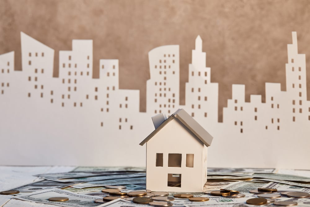 Small cardboard house on coins and cash, paper skyline in background