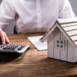 Close-up of person using calculator on desk, house model beside
