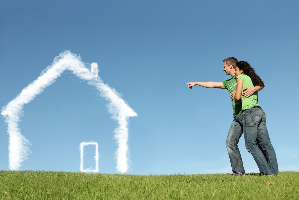 Couple outside, looking at clouds forming a house outline