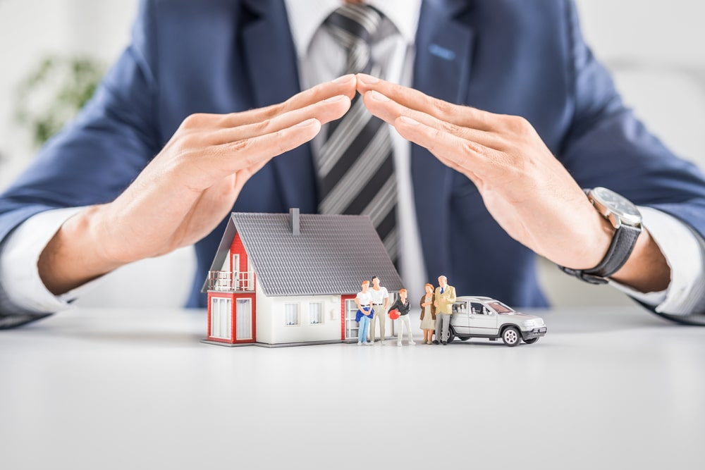 Man in suit holding hands over tiny house model, family, and car