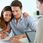 Young couple signing real estate contract
